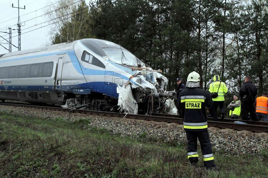 Emergency services work at the scene where a collision of a train and a lorry in south Poland on April 7, 2017.