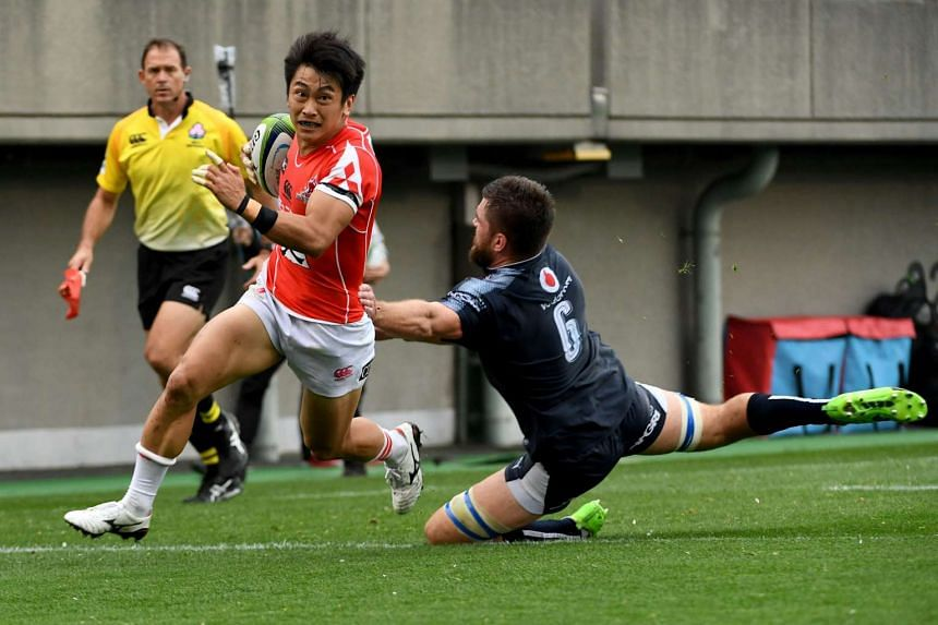 Takaaki Nakazuru of the Sunwolves carries the ball past a tackle by Nick de Jager of the Bulls during the Super Rugby match between the Sunwolves of Japan and the Bulls of South Africa at Prince Chichibu Memorial stadium in Tokyo on April 8, 2017.