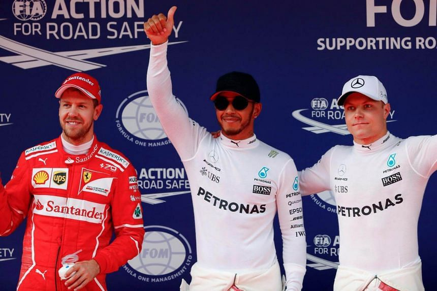 Mercedes driver Lewis Hamilton (centre) of Britain reacts after setting pole position in qualifying alongside team mate Valtteri Bottas (right) of Finland and Ferrari's Sebastian Vettel of Germany at the Shanghai International Circuit.