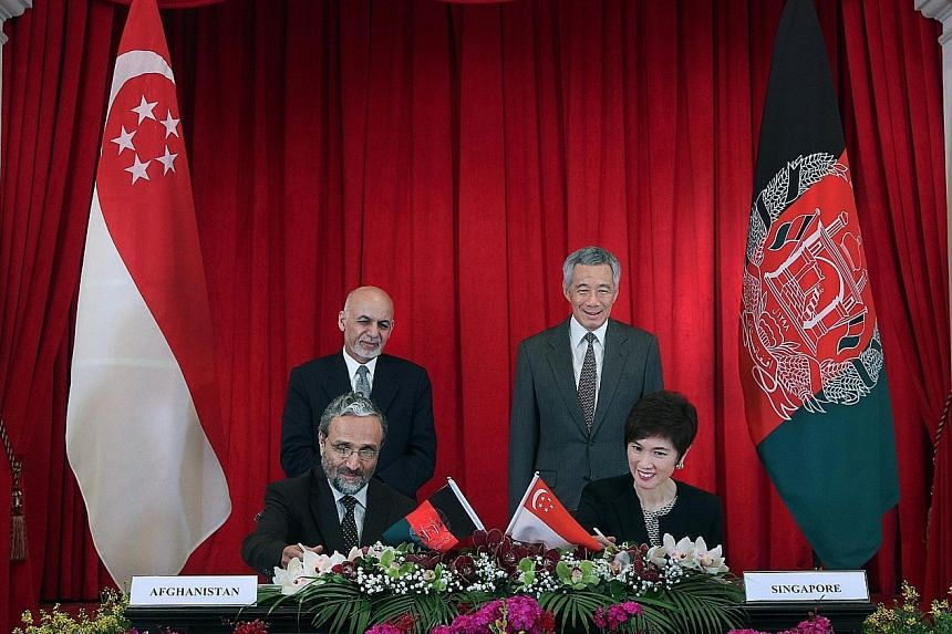 Prime Minister Lee Hsien Loong and Afghan President Mohammad Ashraf Ghani witnessing the signing of the MOU by Mrs Josephine Teo, Senior Minister of State, Prime Minister's Office, Ministry of Foreign Affairs and Ministry of Transport; and Afghan Min