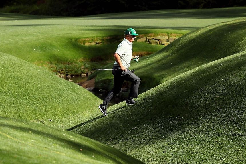 Charley Hoffman jogs up the par-five 13th during the first round of the Masters. He parred the hole en route to a 65.