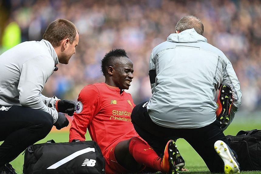 Liverpool forward Sadio Mane receiving treatment on his knee after getting involved in a challenge with Everton's Leighton Baines. Mane's absence for the rest of the season will be a massive blow to the Reds' top-four hopes.