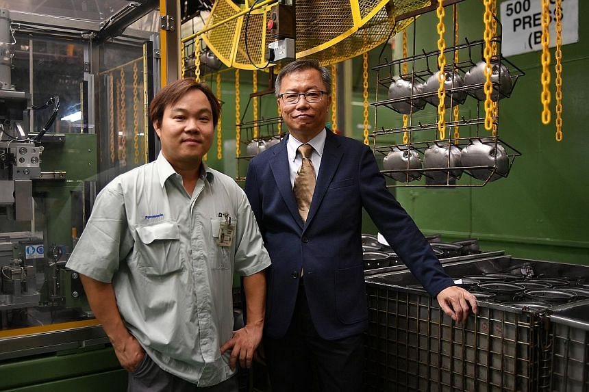 Panasonic employees Ng Wee Teck (left) and Khoo Chew Thong were lauded by Minister for Manpower Lim Swee Say for upgrading their skills to keep up with advances in technology.