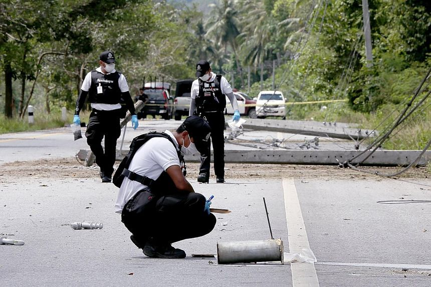 Thai forensic police officers inspecting bomb-damaged power poles at a blast scene in the southern province of Pattani yesterday. Arson and bomb attacks caused widespread blackouts in four southern provinces.