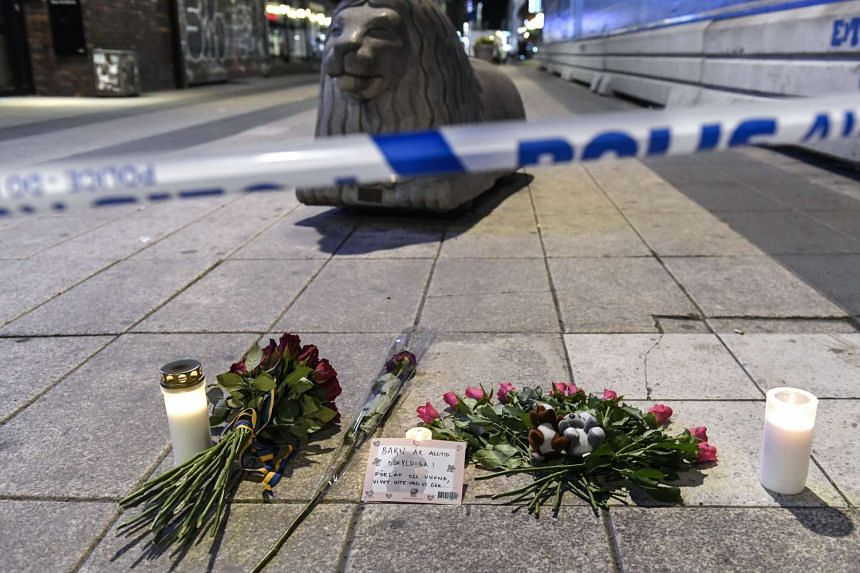 Candles and flowers near the site where a beer truck crashed into the Ahlens department store after plowing down the Drottninggatan Street in central Stockholm, Sweden, on April 7, 2017.