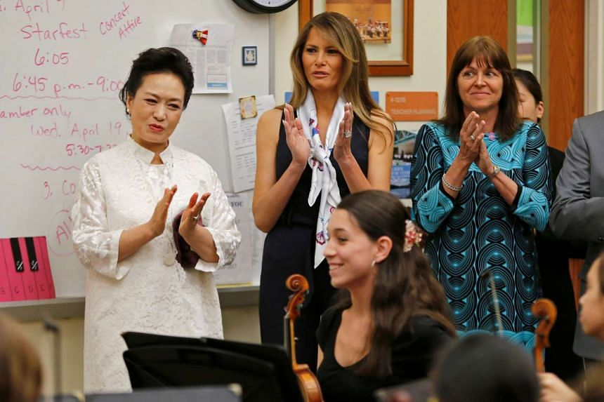 US First Lady Melania Trump and China's First Lady Peng Liyuan applaud after students performed for them at Bak Middle School of the Arts in West Palm Beach, Florida, US, on April 7, 2017.