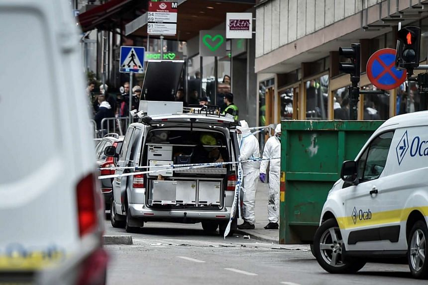 Forensic police investigators work at the crime scene in central Stockholm on April 8, 2017, a day after a truck plowed into pedestrians on Drottninggatan.