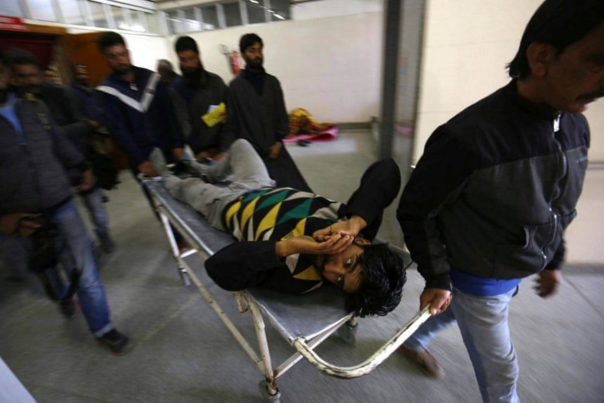 An injured young man is carried out as massive protests broke out in the Srinagar-Budgam parliamentary constituency.