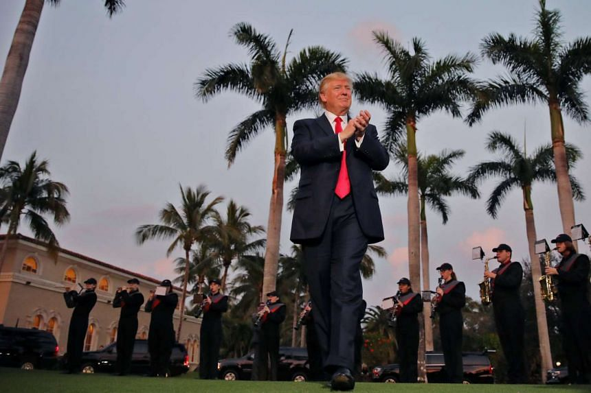 Trump applauds as a marching band performs at Trump International Golf club in West Palm Beach, Florida, Feb 5, 2017.
