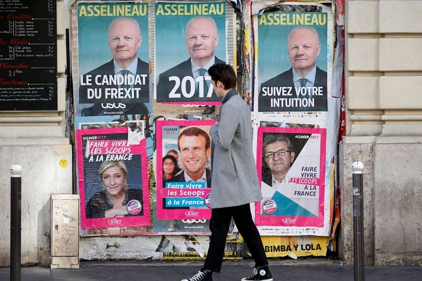A pedestrian walks past campaign posters for the 2017 French presidential election, in Paris, on April 2, 2017.