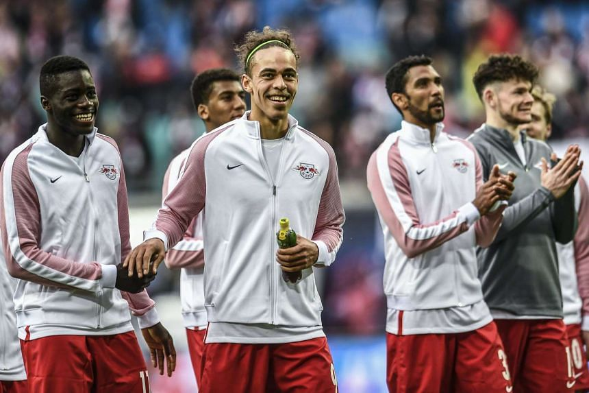 Leipzig's Yussuf Poulsen (centre) and his teammates celebrate their victory.