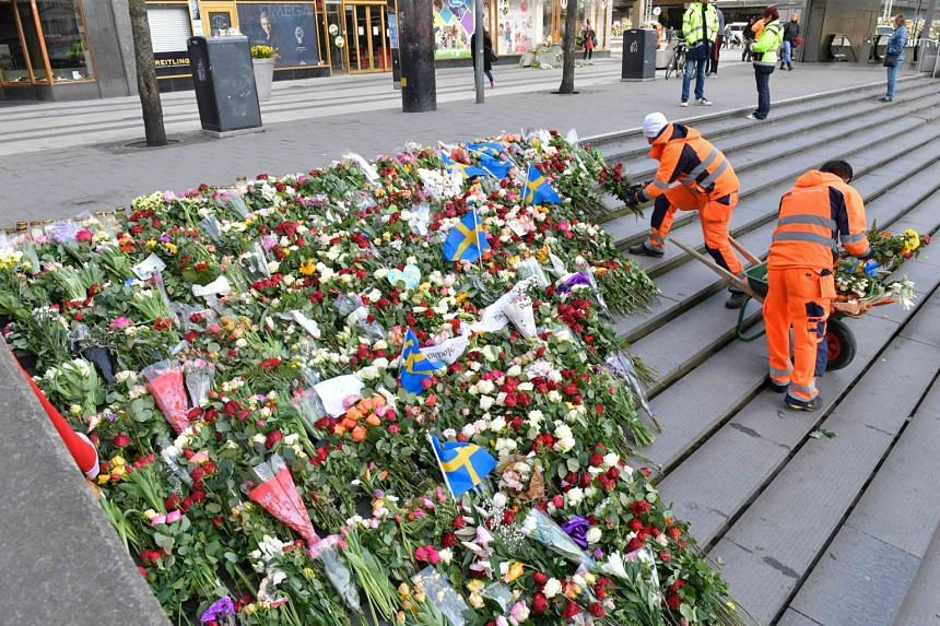 Workers place flowers and candles at the steps of Sergels Torg plaza in tribute to the victims of the attack.