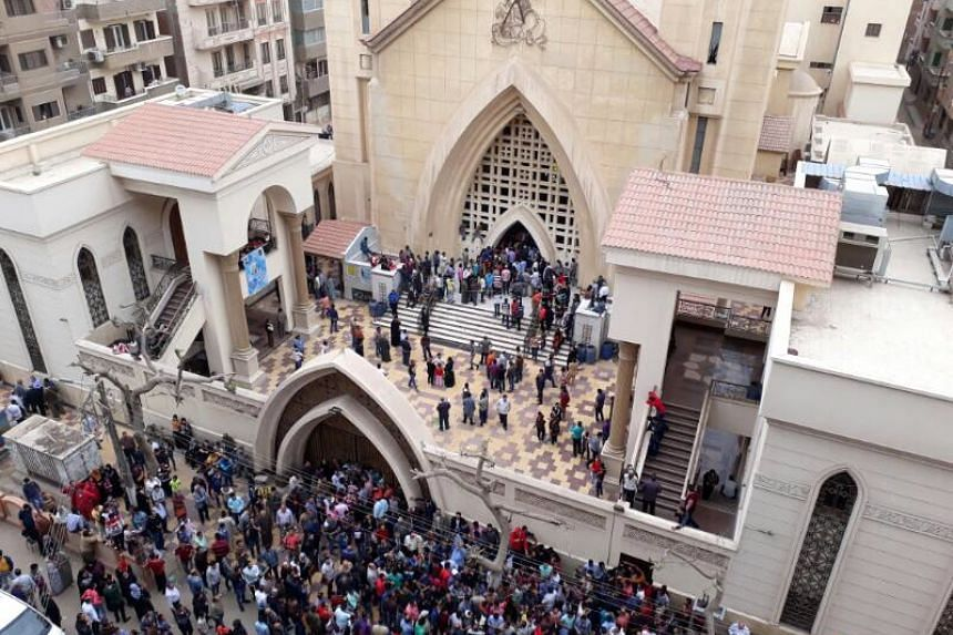 People gather in front of Mar Girgis church after a bomb explosion.