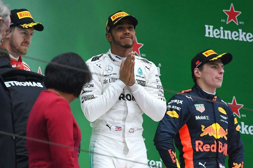 Lewis Hamilton on the podium between second-placed Sebastian Vettel (left) and third-placed Max Verstappen (right).