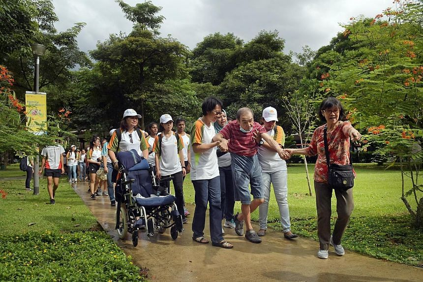 """Madam Rebecca Wong, 65, leading the way to encourage her husband, Mr Tay Yam Hwee, 71, at a mass walk yesterday at the Toa Payoh Town Park, during the Parkinson Society Singapore's annual """"Move to Beat Parkinson"""" Day. The event, now in its fourth yea"""