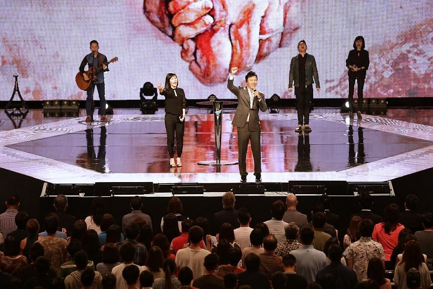 City Harvest Church pastor Kong Hee on stage with his wife Ho Yeow Sun at the church's weekend service yesterday, a day after the six church leaders had their sentences generally halved on appeal.