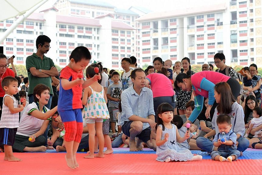 Mrs Josephine Teo (seated, far left) joins the families in a mass song and dance activity at the inaugural event at Bishan Active Park yesterday.