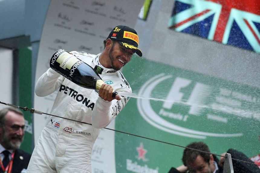Lewis Hamilton celebrates with champagne on the podium after winning the Formula One Chinese Grand Prix.