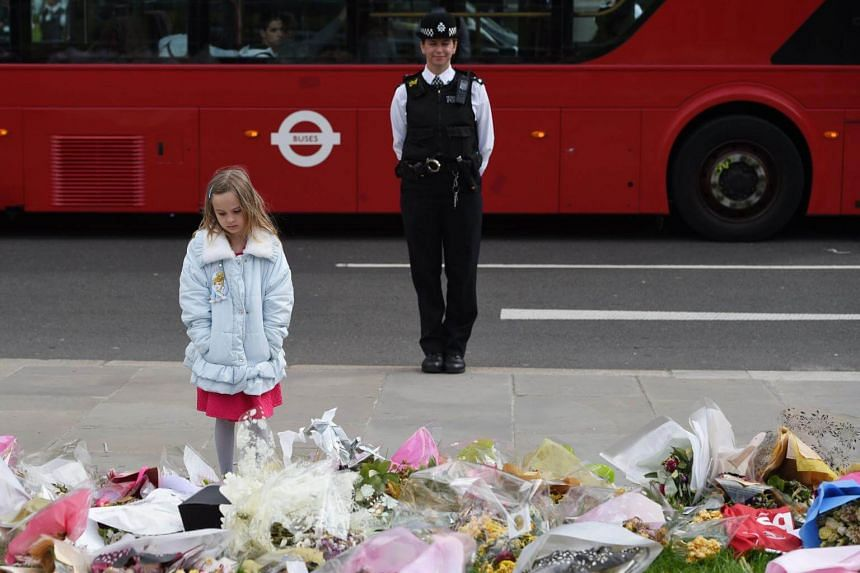 A girl looks at floral tributes for PC Keith Palmer during the funeral parade outside Parliament in London, Britain, on April 10, 2017.