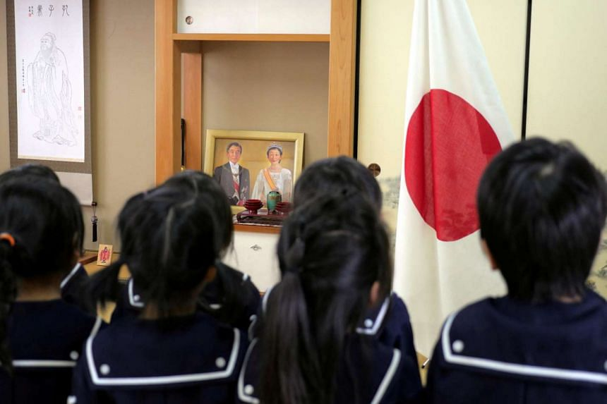 Students recite the Imperial Rescript on Education and Confucian Analects in front of Japan's national flag, a picture of Japanese Emperor Akihito and Empress Michiko, and a hanging scroll of Confucius at Tsukamoto kindergarten in Osaka, Japan on No