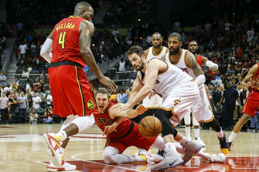 Atlanta Hawks forward Mike Muscala (31) pushes the ball to forward Paul Millsap (4) past Cleveland Cavaliers forward Kevin Love (0) in the fourth quarter at Philips Arena.