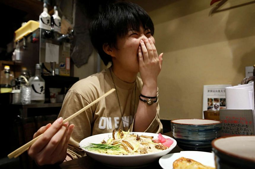 A customer smiles as she eats an 'Insect tsukemen' ramen noodle topped with fried worms and crickets at 'Ramen Nagi' restaurant in Tokyo, Japan on April 9, 2017.