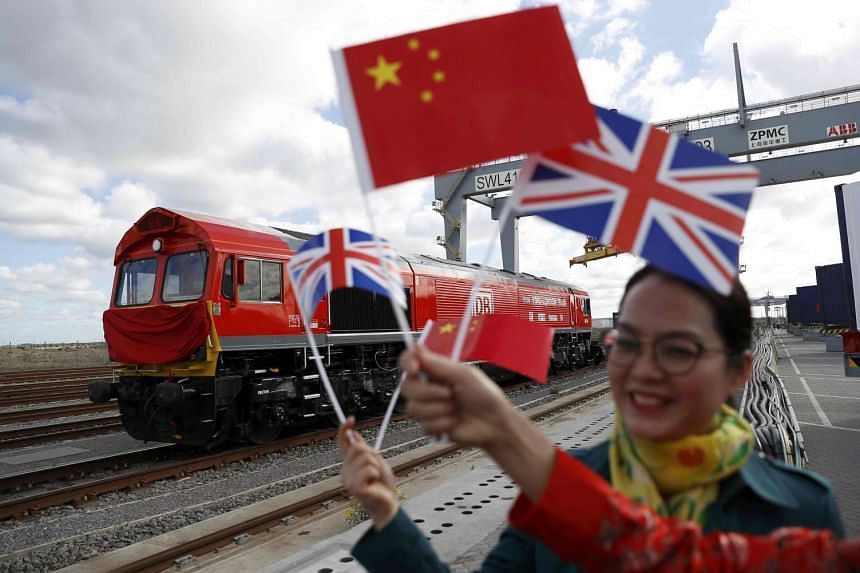 Women wave flags at the ceremony to mark the departure of the first freight train to run from Britain to China.