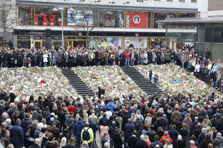 People observe a minute of silence at noon during a remembrance service on Sergels Torg, in Stockholm, Sweden, on April 10, 2017.