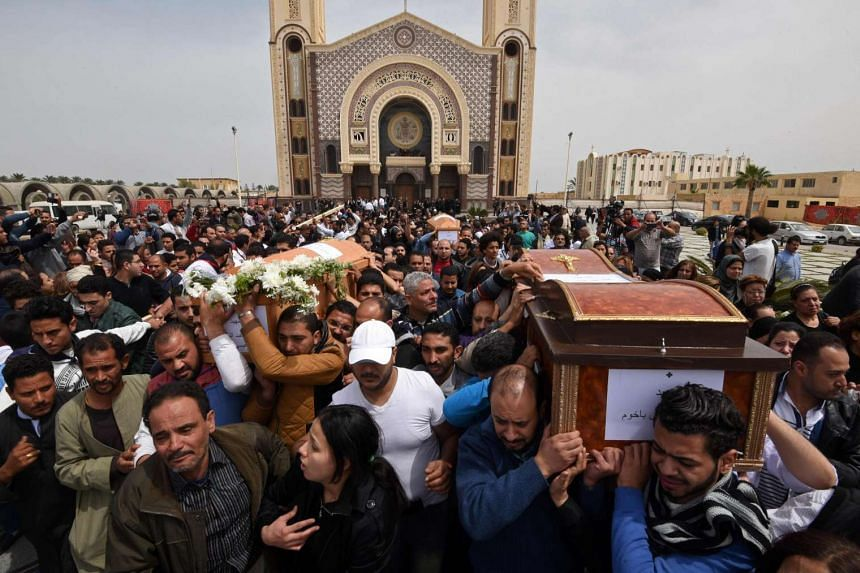 Mourners carry the coffins of victims of the attack at the Coptic church in Alexandria.