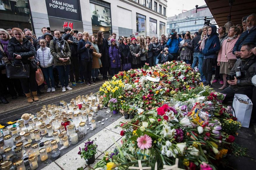 People observe a minute of silence to commemorate the victims of a terror attack at a makeshift memorial near the site where a truck drove into Ahlens department store in Stockholm on April 10, 2017.