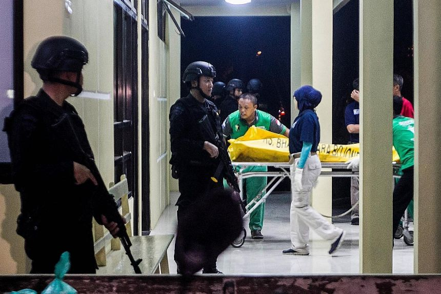A bag containing the body of a suspected militant arriving at a police hospital in Surabaya on Saturday, as Indonesian anti-terror police officers stood guard.