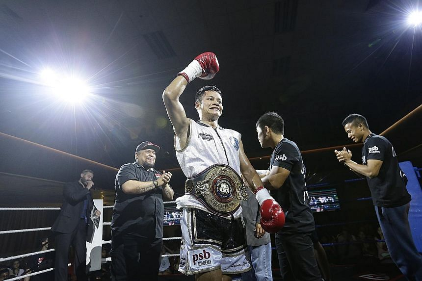 Muhamad Ridhwan celebrating his World Boxing Association Asia Featherweight Championship title win - the first Singaporean to hold the belt - after knocking out Indonesia's Waldo Sabu in the second round on Saturday night.