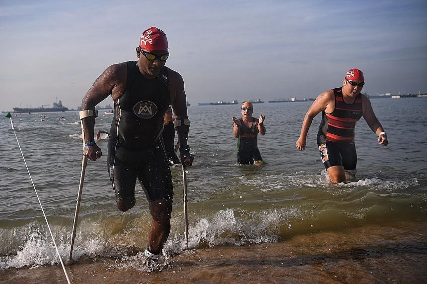 Amputee Abdul Alim, 44, taking part in the 2km men's open/ veteran swim category at the Tri-Factor Series held yesterday morning at East Coast Park. Erasmus Ang, 17, won the 2km open water swim race in 30min 32sec, while Amos Tan, 46, won the 2km vet