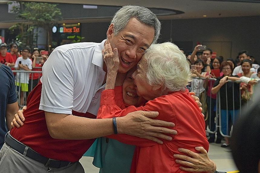 Prime Minister Lee Hsien Loong with Mrs Therese Stewart and her daughter Olivia shortly after he paid tribute to Mrs Stewart's late husband Stanley - a former head of the civil service - at the Eurasian Festival at Tampines Hub yesterday.
