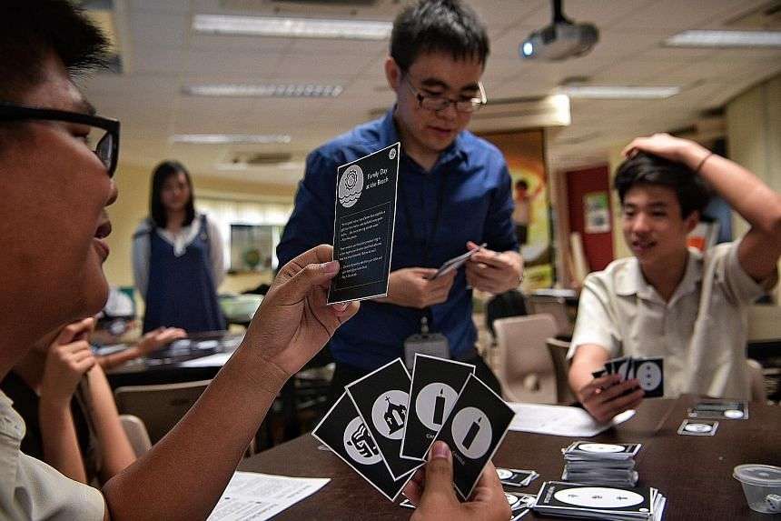 Bukit Batok Secondary School students Calvin Lim (with spectacles) and Edgar Pang, both 16, play a card game based on the book The Joy Luck Club under the tutelage of their teacher Ow Yeong Wai Kit.