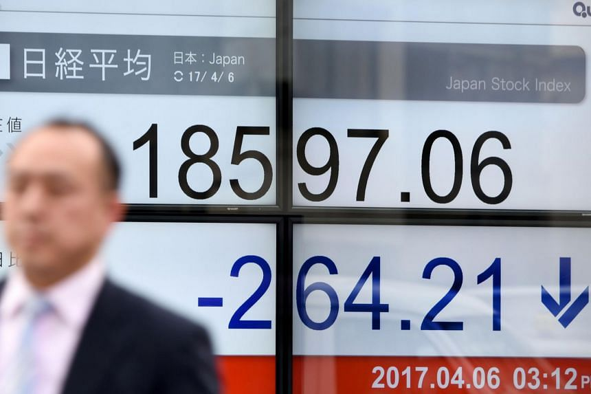 A businessman walking past a stock quotation board flashing the Nikkei 225 key index of the Tokyo Stock Exchange in front of a securities company in Tokyo on April 6, 2017.
