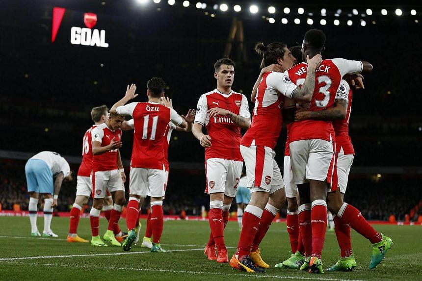 Arsenal's English midfielder Theo Walcott celebrating with teammates after scoring their second goal during the English Premier League football match between Arsenal and West Ham United, on April 5, 2017.