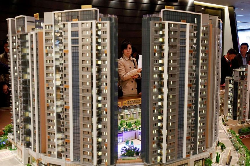 A potential buyer looking at a model of Riva, one of the latest developments by Sun Hung Kai Properties, in Hong Kong, on Feb 19, 2014.