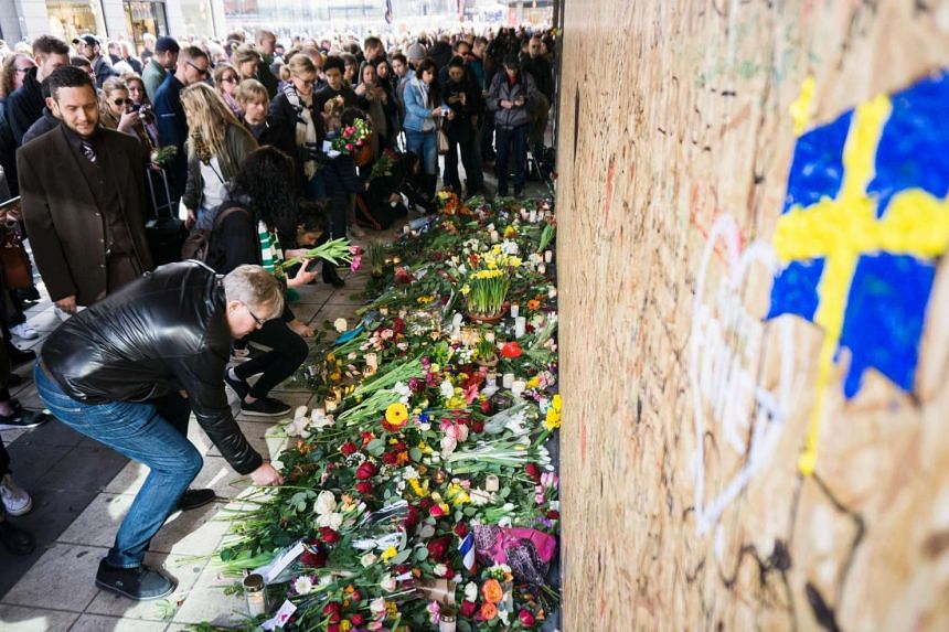 People gather around a plywood wall at a makeshift memorial where a truck drove into a department store in Stockholm.