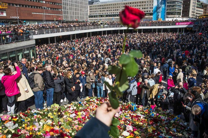 People attend a memorial ceremony on April 9, 2017 at Sergels Torg plaza in Stockholm, near the site of the attack.