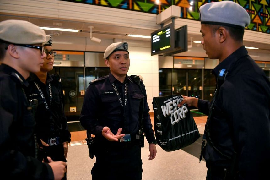 Staff Sergeant Nasron Nasir (centre) talking to another TransCom officer about a plastic bag apparently left behind by a train commuter.