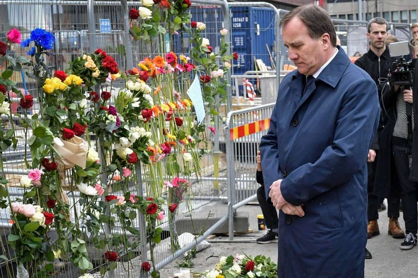Swedish Prime Minister Stefan Lofven looks at flowers near the scene of a truck attack in central Stockholm, Sweden, on April 8, 2017, the day after the hijacked beer truck ploughed into pedestrians on Drottninggatan and crashed into Ahlens departmen