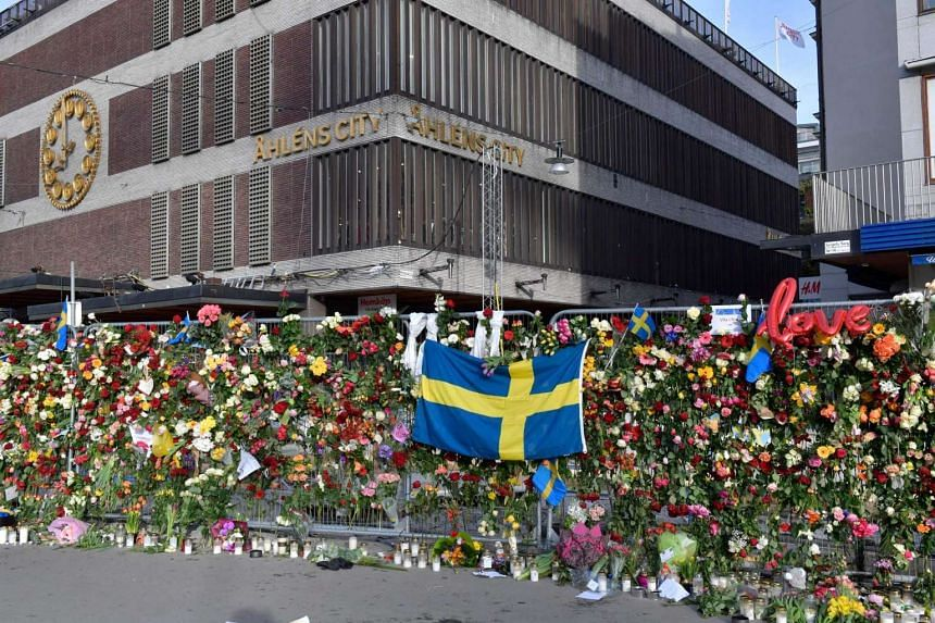 A Swedish flag, floral tributes and candles on a fence by the department store, Ahlens, beside the scene of a truck attack in Stockholm, Sweden, on April 9, 2017.