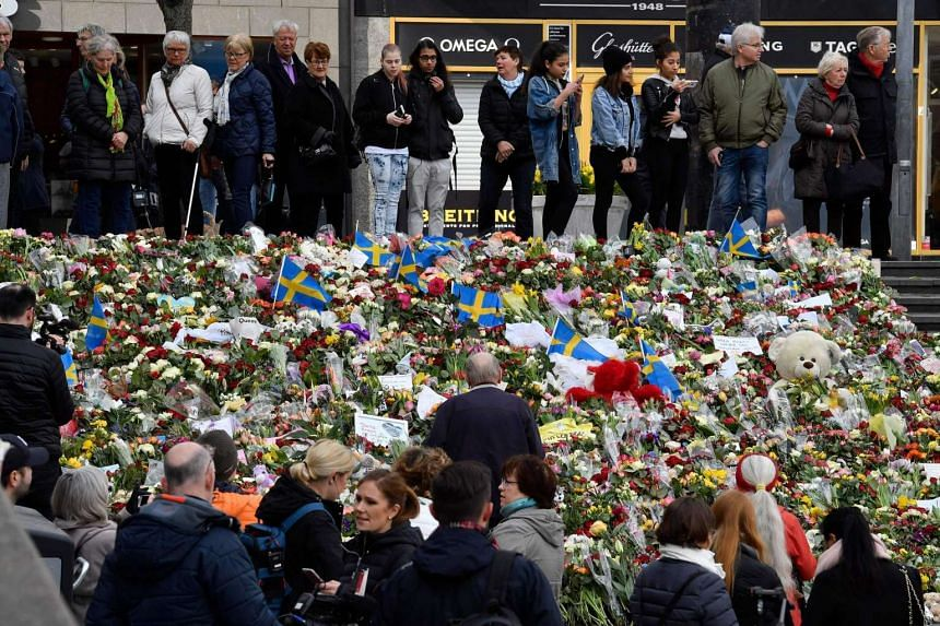 People leave floral tributes on the steps at Sergels Torg public square, for victims of a truck attack in central Stockholm, Sweden, April 9, 2017.