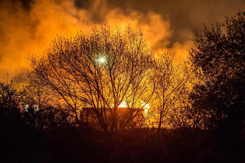 """A huge fire blazes through the Grande-Synthe migrant camp outside the northern French city of Dunkirk late April 10, 2017, reducing it to """"a heap of ashes"""", the regional chief said."""