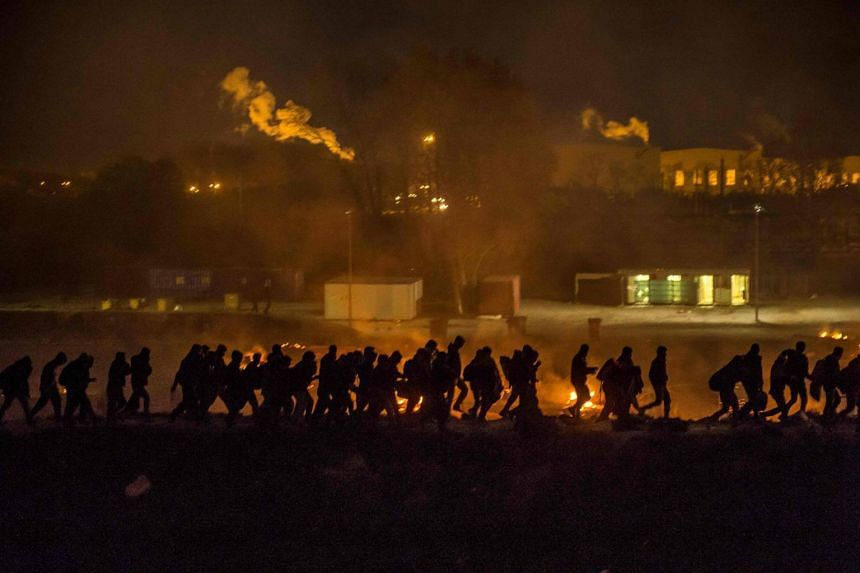 """Migrants evacuate as a huge fire blazes through the Grande-Synthe migrant camp outside the northern French city of Dunkirk late April 10, 2017, reducing it to """"a heap of ashes"""", the regional chief said."""