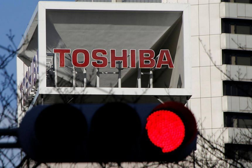 The logo of Toshiba Corp is seen behind a traffic signal at its headquarters in Tokyo, Japan, on Jan 27, 2017.
