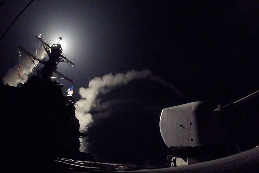 A handout photo made available by the US Navy Office of Information shows the guided-missile destroyer USS Porter (DDG 78) launching a missile strike while in the Mediterranean Sea, on April 7, 2017.