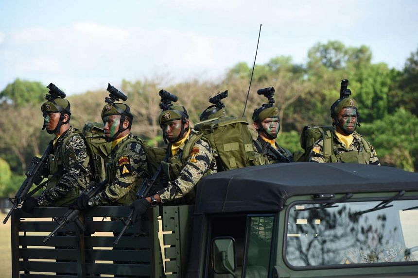 In this photo taken on April 4, 2017 Philippine army soldiers stand aboard a vehicle during a march and review as part of their anniversary celebration at Fort Bonifacio in Manila.
