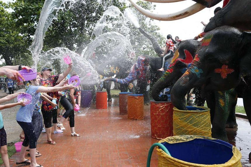 Foreign revelers battle water with elephants during a preview of Songkran Festival celebration, the Thai traditional New Year at the ancient world heritage historical park in city of Ayutthaya province, 